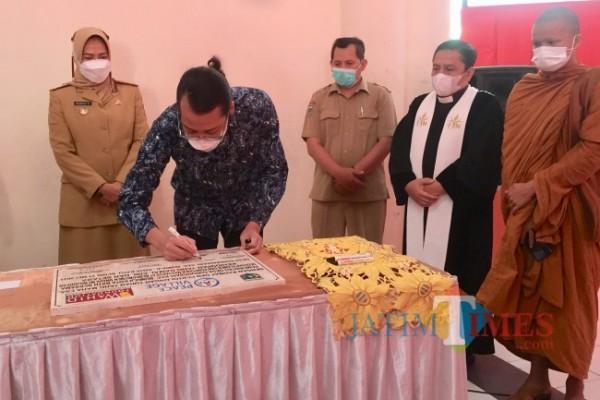 Direktur Eksekutif Wahid Foundation Mujtaba Hamdi saat menandatangani prasasti disaksikan oleh 5 pemuka agama di Pendapa Kecamatan Bumiaji, Senin (31/5/2021). (Foto: Irsya Richa/MalangTIMES)