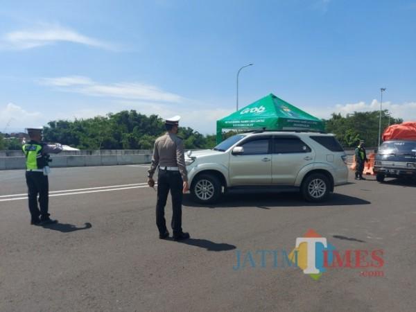 Petugas kepolisian saat mengarahkan pengendara untuk putar balik di Exit Tol Madyopuro Kota Malang. (Foto: Tubagus Achmad/MalangTIMES)