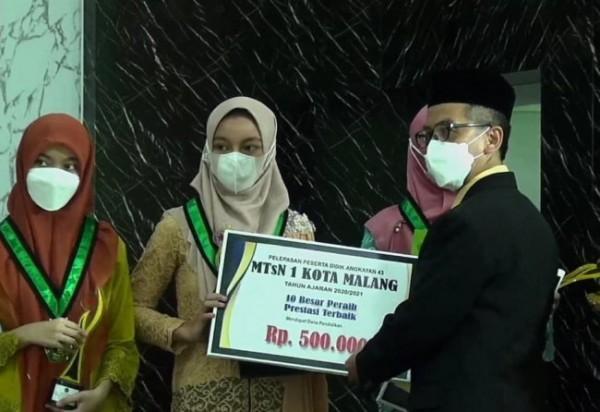 Kepala MTsN 1 Kota Malang, Drs H Samsudin MPd menyerahkan penghargaan dalam Penobatan 10 Besar Penyumbang Prestasi Terbanyak MTsN 1, Jumat (4/6/21). (Foto: Istimewa)