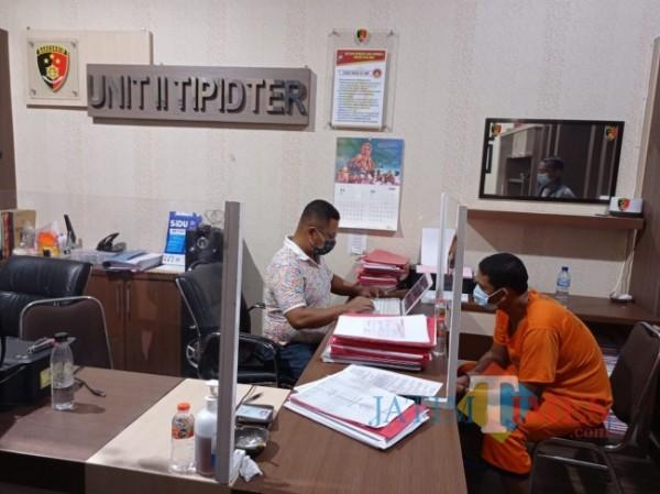 Pelaku pembunuhan (baju oranye) saat diperiksa penyidik Unit II Tipidter Satreskrim Polres Malang (foto: Hendra Saputra/MalangTIMES)