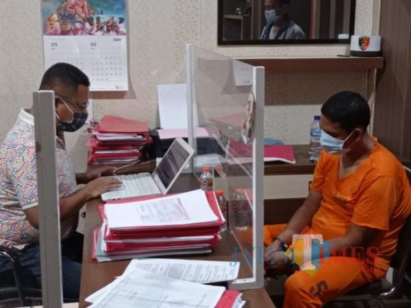 Tersangka Ali Muddin (kanan) saat diperiksa penyidik Unit II Tipidter Satreskrim Polres Malang (foto: Hendra Saputra/MalangTIMES)