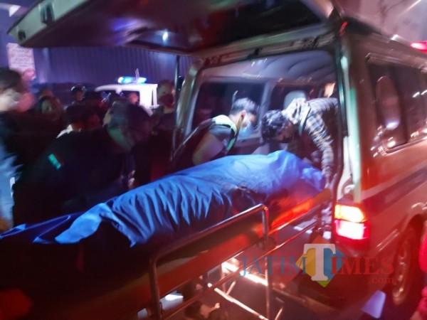 Jenazah korban atas nama Sudarsono (60) warga Jalan Kolonel Sugiono Gang 6, Kelurahan Ciptomulyo, Kecamatan Sukun, Kota Malang yang di evakuasi ke dalam mobil ambulans, Jumat (4/6/2021) malam. (Foto: Tubagus Achmad/MalangTIMES)