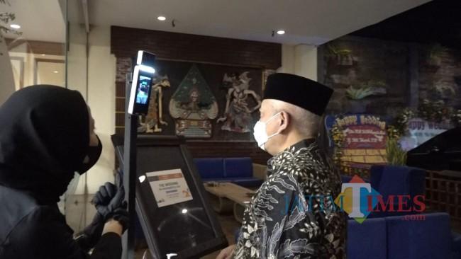 Bupati Malang Muhammad Sanusi saat melakukan pengecekan suhu.