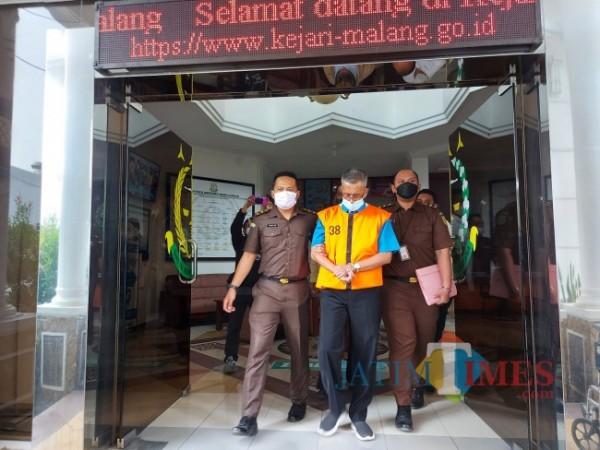Kepala Sekolah SMKN 10 Malang Dwidjo Lelono (rompi oranye) saat keluar dari Kejaksaan Negeri Kota Malang, Senin (7/6/2021). (Foto: Tubagus Achmad/MalangTIMES)