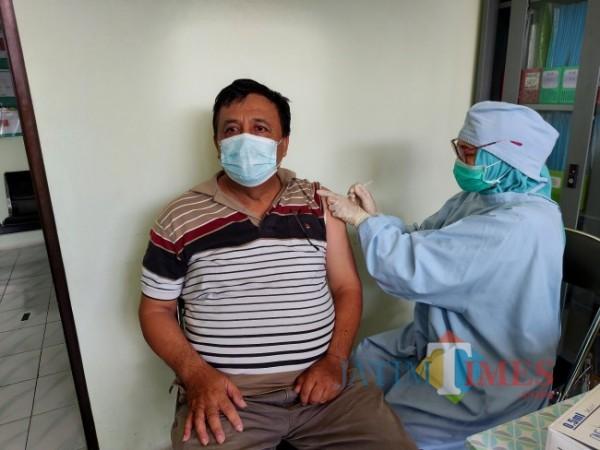 Salah seorang warga yang tergolong lansia bernama Wahyu Edi Sasmito (60) saat menjalani vaksinasi Covid-19 di Puskesmas Bareng, Selasa (8/6/2021). (Foto: Tubagus Achmad/MalangTIMES)