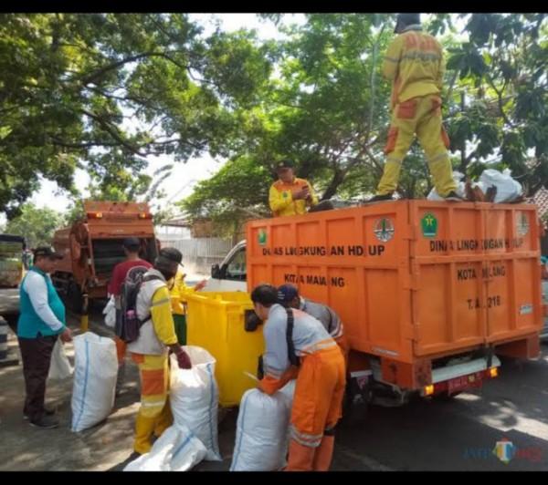 Petugas DLH Kota Malang saat mengangkut sampah. (Foto: Dokumentasi JatimTIMES).