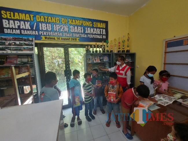 Anak-anak saat menikmati koleksi buku dari Kampung Sinau, Kelurahan Sawojajar, Kecamatan Kedungkandang, Kota Malang.