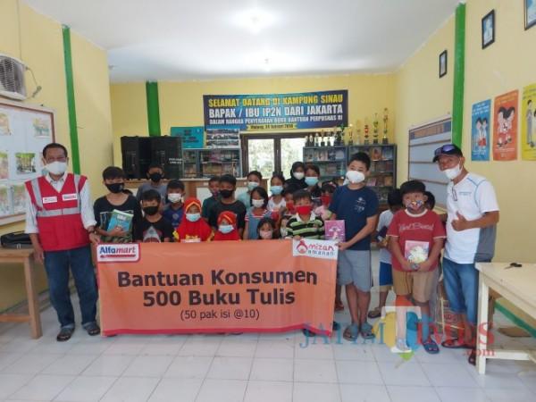 Corporate Communication Regional Manager PT Sumber Alfaria Trijaya M. Faruq Asrori (paling kiri) saat berfoto bersama anak-anak usai memberikan buku tulis di Kampung Sinau, Sabtu (12/6/2021). (Foto: Tubagus Achmad/MalangTIMES)