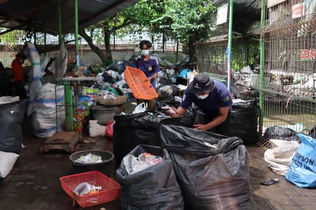 Petugas Bank Sampah (BSM) sebagai mitra Dinas Lingkungan Hidup saat melakukan penyortiran sampah plastik untuk didaur ulang.