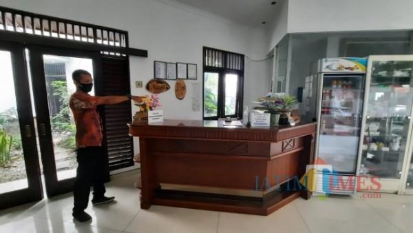 Petugas Tlogomas Guest House saat menunjukkan lokasi pencurian uang di meja resepsionis, Selasa (15/6/2021). (Foto: Tubagus Achmad/MalangTIMES)