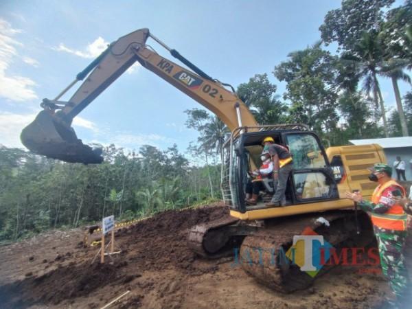 Bupati Malang HM Sanusi saat menjalankan alat berat sebagai tanda dimulainya berjalannya proyek Embung Peniwen (foto: Hendra Saputra/MalangTIMES)
