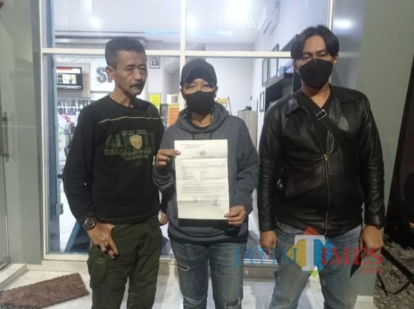 Korban MT (tengah) saat menunjukkan laporan polisi di Mapolresta Malang Kota, Jum'at (18/6/2021) dini hari (foto: Hendra Saputra/ MalangTIMES)