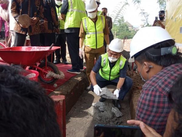 Sekretaris Komisi D DPRD Kota Malang Rokhmad saat turut andil dalam kegiatan peletakan batu pertama dalam pembangunan SMPN 29 Malang. (Ist)