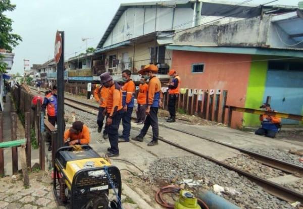Petugas dari PT KAI Daop 8 Surabaya saat melakukan penutupan palang perlintasan kereta api liar di Kota Malang, Senin (28/6/2021). (Foto: Humas PT KAI Daop 8 Surabaya)