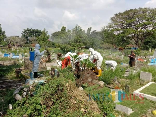 Petugas dari UPT Pemakaman Dinas Lingkungan Hidup Kota Malang, BPBD Kota Malang dan PSC Kota Malang saat memakamkan jenazah Covid-19 beberapa waktu lalu. (Foto: Tubagus Achmad/ MalangTIMES)