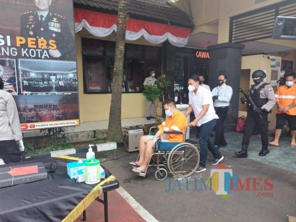 Tersangka Jefrie Permana (36) gunakan kursi roda saat dihadirkan didepan awak media di Polresta Malang Kota, Senin (28/6/2021). (Foto: Tubagus Achmad/MalangTIMES)
