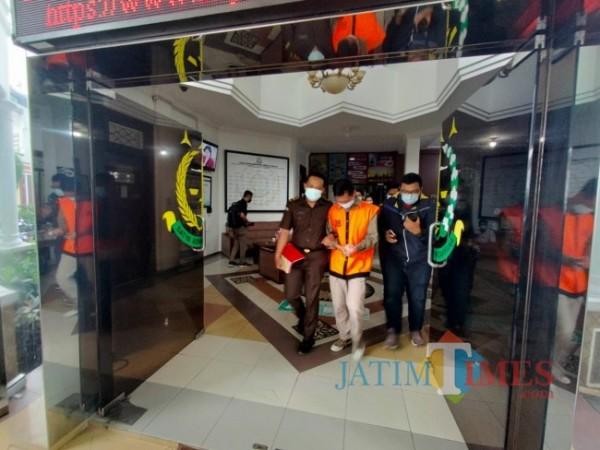 Tersangka berinisial AR (rompi oranye) saat dibawa keluar dari Kantor Kejaksaan Negeri Kota Malang, Senin (28/6/2021). (Foto: Tubagus Achmad/ MalangTIMES)