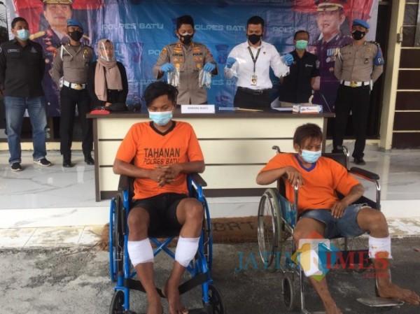 Dua tersangka duduk di atas kursi roda di Mapolres Batu, Selasa (29/6/2021). (Foto: Irsya Richa/MalangTIMES)