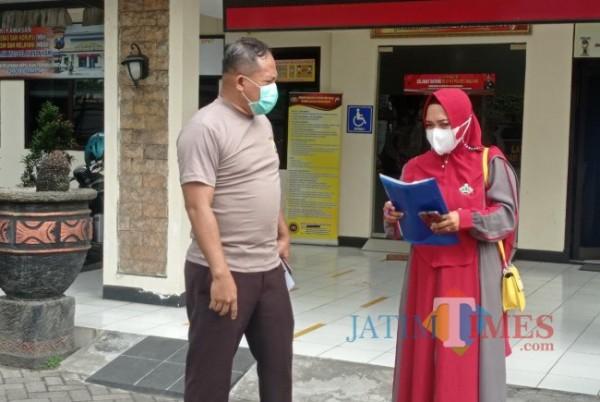 IA (kanan) berbincang dengan salah satu anggota Polres Malang saat akan melaporkan arisan online fiktif yang sempat diikutinya. (foto: Hendra Saputra/MalangTIMES)