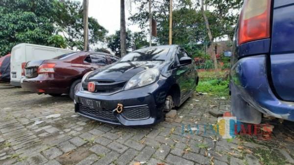 Kondisi mobil Honda Brio yang terparkir di Lapangan Merjosari dan keempat bannya hilang dicuri maling, Rabu (30/6/2021). (Foto: Tubagus Achmad/MalangTIMES)