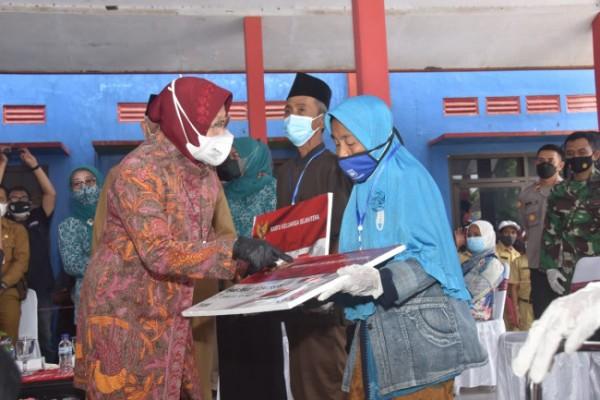 Mensos Tri Rismaharini saat memberikan kartu keluarga sejahtera kepada salah satu korban dugaan penyalahgunaan bantuan PKH. (foto: Humas Pemkab Malang for MalangTIMES)