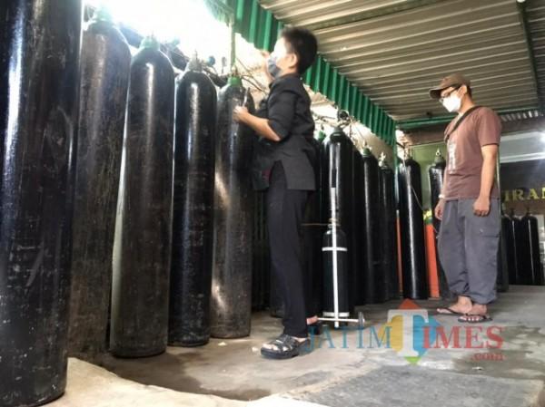 Chandra Atjunita saat melayani pembelian isi ulang gas oksigen di UD Wiranto Gas, Jalan Aris Munandar, Kecamatan Klojen, Kota Malang, Kamis (1/7/2021). (Foto: Tubagus Achmad/MalangTIMES)