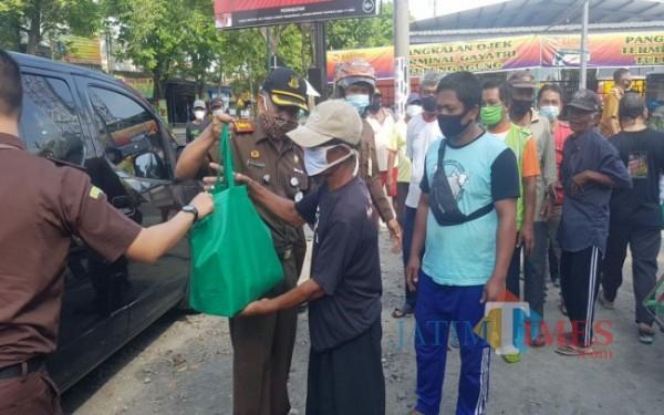 Kejari Tulungagung Mujiarto saat memberikan bantuan Sembako pada tukang becak / Foto : Istimewa / Tulungagung TIMES