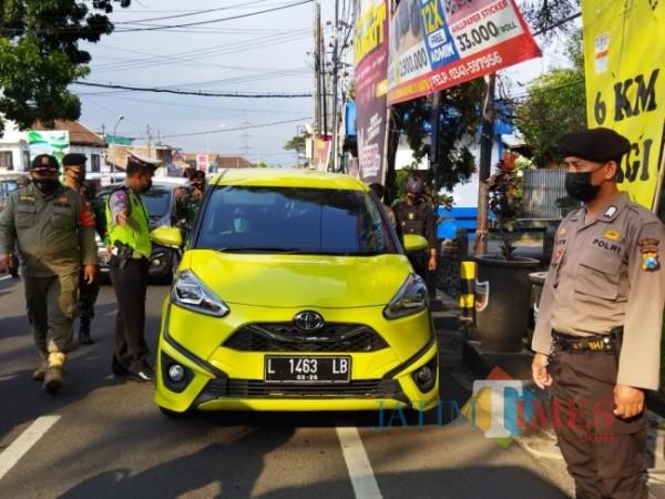 Petugas Polres Batu saat mengecek kendaraan di Pos Pendem, Sabtu (3/7/2021). (Foto: Irsya Richa/MalangTIMES)