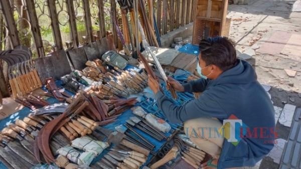 Miftahur Rohman, Salah Seorang Penjual pisau saat menunjukan dagangannya kepada pembeli di Kawasan Pasar Rogojampi Banyuwangi (Nurhadi Banyuwangi/BanyuwangiTIMES)