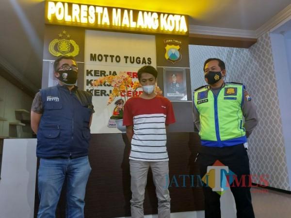 Pelaku penyebar hoax Aji Prasetyo Utomo (23) saat didampingi pihak kepolisian saat memberikan klarifikasi dihadapan awak media di Mapolresta Malang Kota, Senin (5/7/2021) malam. (Foto: Tubagus Achmad/MalangTIMES)