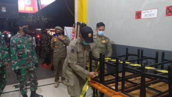Petugas saat melakukan pendisiplinan penindakan salah satu tempat usaha yang melanggar aturan PPKM Darurat di Kota Malang. (Foto: Istimewa).