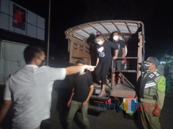 Anggota Polres Malang dan Satpol PP Kabupaten Malang saat menurunkan warga yang nekat keluar malam dan buka usaha malam hari di masa PPKM Darurat (foto: Hendra Saputra/MalangTIMES)