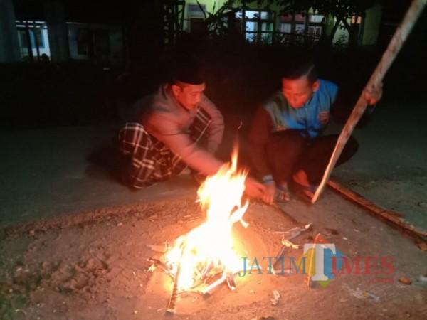 Warga sedang membuat kobaran api untuk membakar garam (Foto: Abror Rosi/JatimTimes)