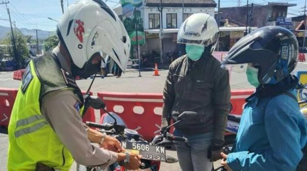 Petugas polisi saat menempelkan stiker kepada kendaraan nakes di Simpang tiga Pendem, Kecamatan Junrejo, Kecamatan Batu (pos penutupan) Minggu (11/7/2021).