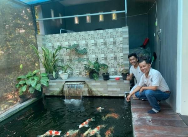 Petani Koi, Robbi Readi (belakang) dan seorang customer yang tengah melihat ikan Koi (depan)(Ist)