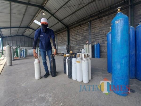Salah satu petugas loket PT Harpag Niaga Hutama sedang menyiapkan tabung oksigen satu meter kubik untuk diisi ulang, Senin (12/7/2021). (Foto: Tubagus Achmad/MalangTIMES)