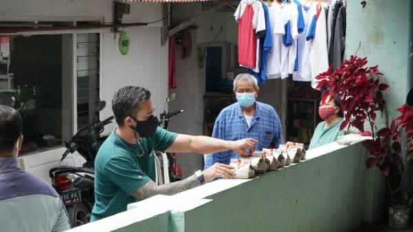 Owner Hill House Arief Utama Waworuntu bersama Polres Batu berkeliling membagikan nasi bungkus di area Malang Raya. (Foto: istimewa)