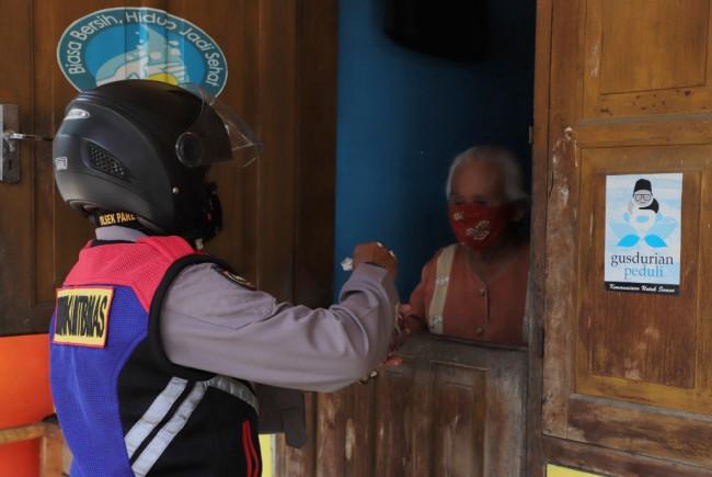 Petugas dari Polres Kediri menyerahkan daging hewan kurban ini secara door to door kepada warga yang berhak menerima. (Foto: Ist)