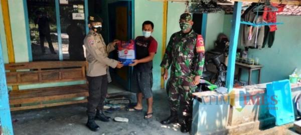 Bhabinkamtibmas Kepolisian Sektor Ngawi, bagikan bansos berupa beras kepada warga di Desa Ngawi yang terdampak Covid-19