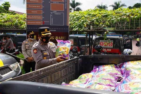 Kapolsek Bululawang, Kompol Pujiyono saat menata beras yang akan disalurkan kepada masyarakat (foto: Humas Polres Malang for MalangTIMES)