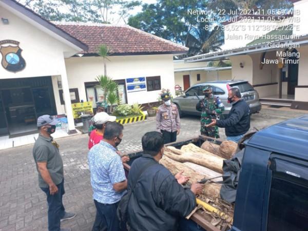 Polisi dan petugas Posal saat melihat kayu yang jadi barang bukti ilegal logging di Mapolsek Gedangan (foto: istimewa)