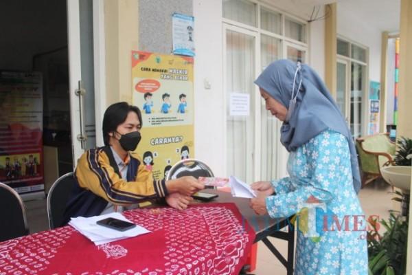 Salah satu warga saat menerima bantuan di Kota Batu. (Foto: Irsya/BatuTIMES)