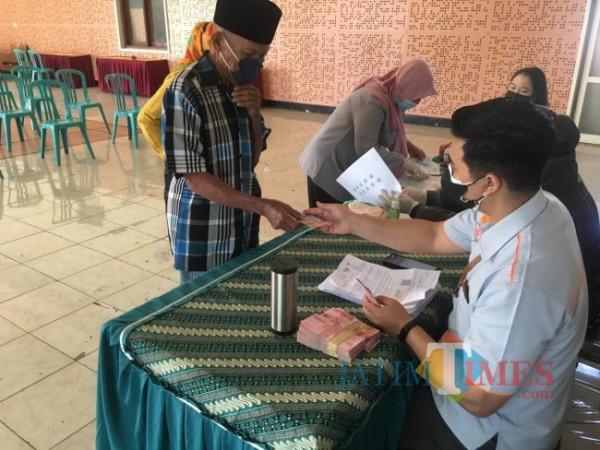 Salah satu warga saat menerima bantuan sosial beberapa sat lalu di Kota Batu.