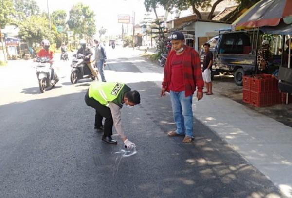 Polisi saat menandai lokasi kecelakaan yang menewaskan bocah 6 tahun di Tumpang. (foto: Satlantas Polres Malang for MalangTIMES)
