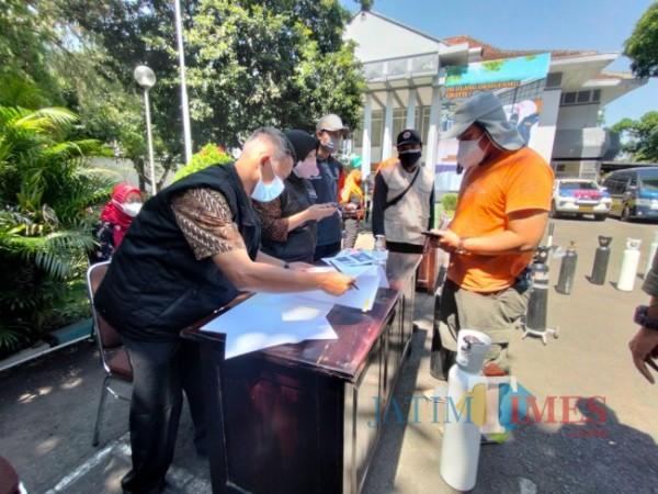 Salah seorang warga yang sedang melakukan registrasi dengan menunjukkan tiket elektronik kepada petugas dari Bakorwil Malang, Senin (26/7/2021). (Foto: Tubagus Achmad/MalangTIMES)