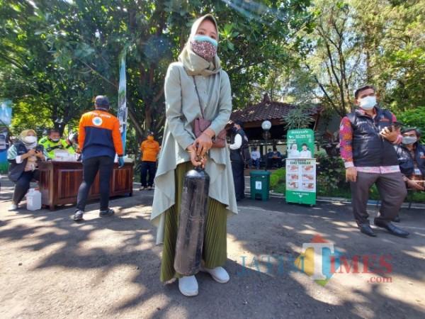 Sosok Qorry Ainah (26) usai mengisi ulang oksigen di depo isi ulang oksigen gratis Bakorwil III Malang, Senin (26/7/2021). (Foto: Tubagus Achmad/MalangTIMES)