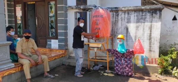Salah satu warga di Desa Menampu saat memasang Prakotan di teras rumah (foto : pitik / Jember TIMES)