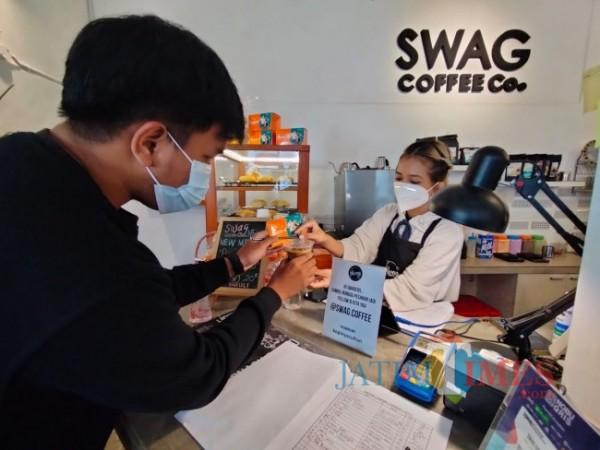 Salah satu pengunjung yang sudah vaksin dan mendapatkan gratis es kopi serta vitamin C dari Swag Cafe, Rabu (28/7/2021). (Foto: Tubagus Achmad/MalangTIMES)