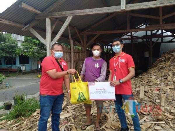 Daduk Budi Susilo, Wakil Kepala Cabang PT Sumber Alfaria Trijaya Tbk (Alfamart) Malang (kiri) saat membagikan sembako kepada warga (Anggara Sudiongko/MalangTIMES)