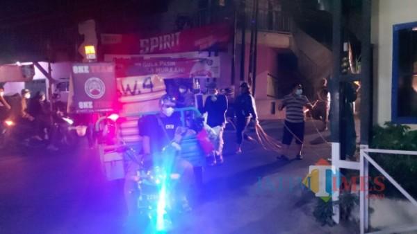Relawan dari Pemuda Tangguh RW. 04, Kelurahan Merjosari, Kecamatan Lowokwaru, Kota Malang saat melakukan penyemprotan desinfektan, Sabtu (31/7/2021) malam. (Foto: Tubagus Achmad/MalangTIMES)